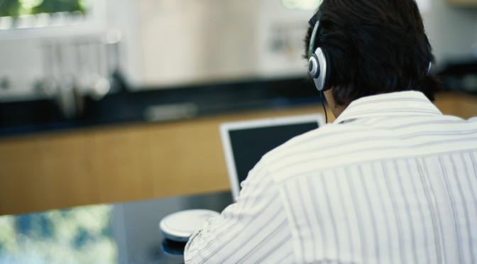 Man wearing headphone using laptop, rear view